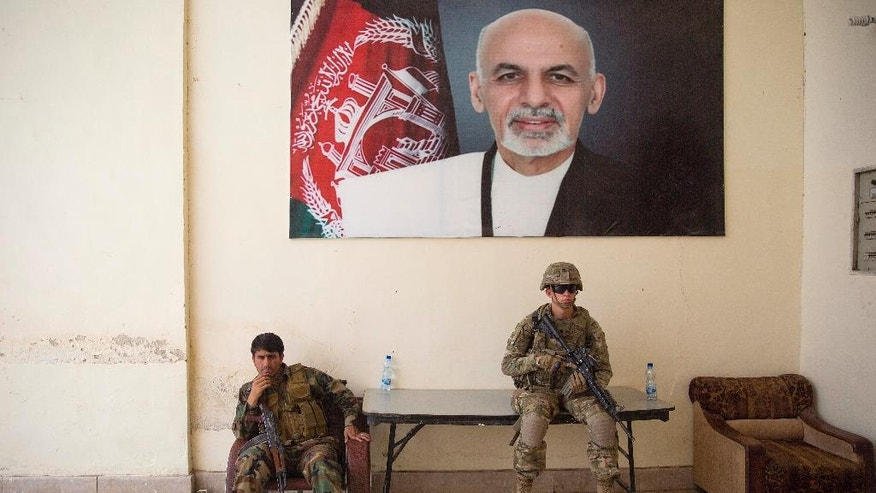 FILE - In this Thursday, Aug. 4, 2016 file photo, an Afghan soldier, left, and a U.S. soldier guard during a visit of Kabul's officials, in the governor's compound in Kandahar, Afghanistan. A new elite Taliban force is proving its strength in the strategic southern province of Helmand, pointing to the insurgents' ability to refine their battlefield techniques to match Afghanistan's increasingly professional national army. (AP Photos/Massoud Hossaini)