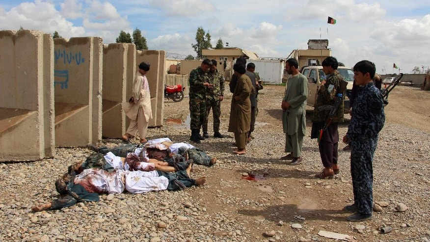 FILE - In this Wednesday, March 9, 2016 file photo, Afghan security forces stand near dead bodies of Taliban insurgents after a complex attack in Helmand province, south west Afghanistan. A new elite Taliban force is proving its strength in the strategic southern province of Helmand, pointing to the insurgents' ability to refine their battlefield techniques to match Afghanistan's increasingly professional national army. (AP Photo/STR)