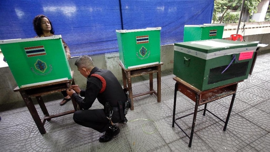 A Thai official and a police prepare booth before vote in a referendum on a new constitution, at a polling station in Bangkok, Thailand, Sunday, Aug. 7, 2016. (AP Photo/Sakchai Lalit)