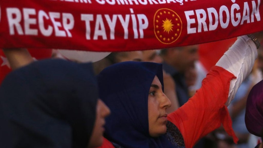 A woman holding a scarf take part at a mass rally in support of Turkey's Prime Minister Recep Tayyip Erodgan following a failed coup that aimed to oust him, in the breakaway Turkish Cypriot half of the capital Nicosia on Friday, Aug. 5, 2016. Mostly right-wing political parties and groups urged supporters to turn up for the rally that follows similar pro-Erdogan and anti-coup demonstrations in other European countries.  (AP Photo/Philippos Christou)