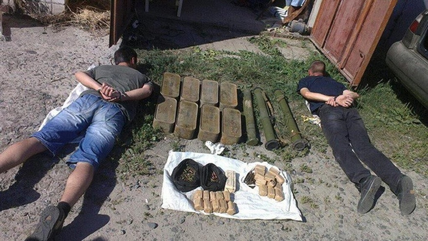 """FOR STORY UKRAINE WEAPONS TRADE -  This Wednesday, July 13, 2016 photo, provided by the Ukrainian Security Service, shows detained weapon dealers and seized weapons in Cherkasy, Ukraine. The war in eastern Ukraine against Russia-backed separatists has led to the uncontrolled spread of firearms throughout the country, with experts describing Ukraine as a """"supermarket"""" where millions of illegal weapons are for sale. (Ukrainian Security Service photo via AP)"""