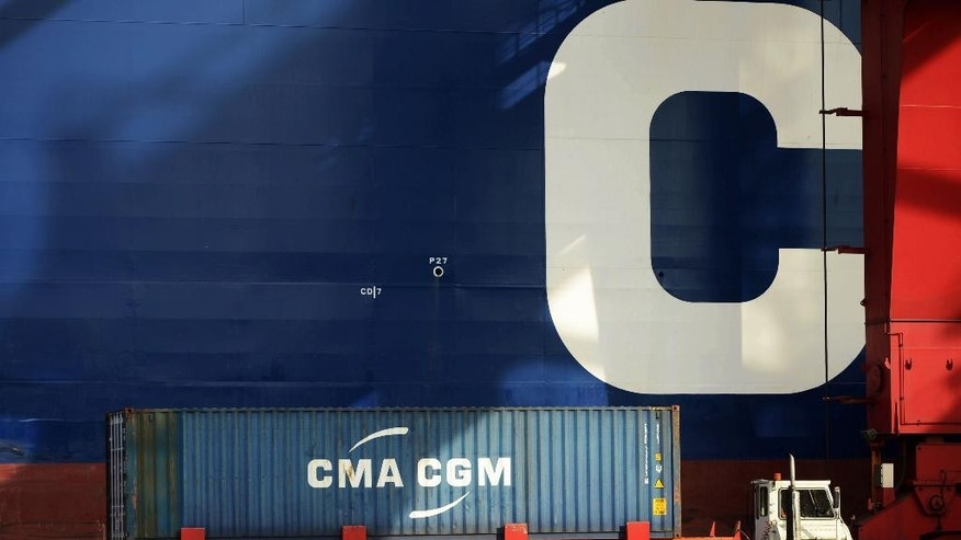 A cargo truck drives past a container ship at a port in Qingdao in eastern China's Shandong province Monday, Aug. 8, 2016. China's exports fell again in July by an unexpectedly wide margin while a decline in imports accelerated in a possible sign of weakness in the world's second-largest economy. (Chinatopix via AP)