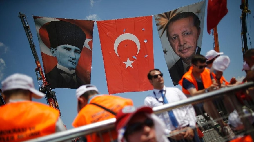 Security personnel stand under the Turkish flag and a portrait of Turkish Republic founder Mustafa Kemal Ataturk, left, and a photograph of the Turkish President Recep Tayyip Erdogan, right, during a Democracy and Martyrs' Rally in Istanbul, Sunday, Aug. 7, 2016. Crowds are gathering in Istanbul for a massive rally to mark the end of nightly democracy demonstrations following Turkey's abortive July 15 coup that killed over 270 people. (AP Photo/Emrah Gurel)