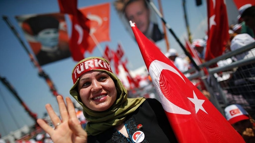 A Turkish woman waves as she holds a flag of her country during a Democracy and Martyrs' Rally in Istanbul, Sunday, Aug. 7, 2016. Crowds are gathering in Istanbul for a massive rally to mark the end of nightly democracy demonstrations following Turkey's abortive July 15 coup that killed over 270 people. (AP Photo/Emrah Gurel)