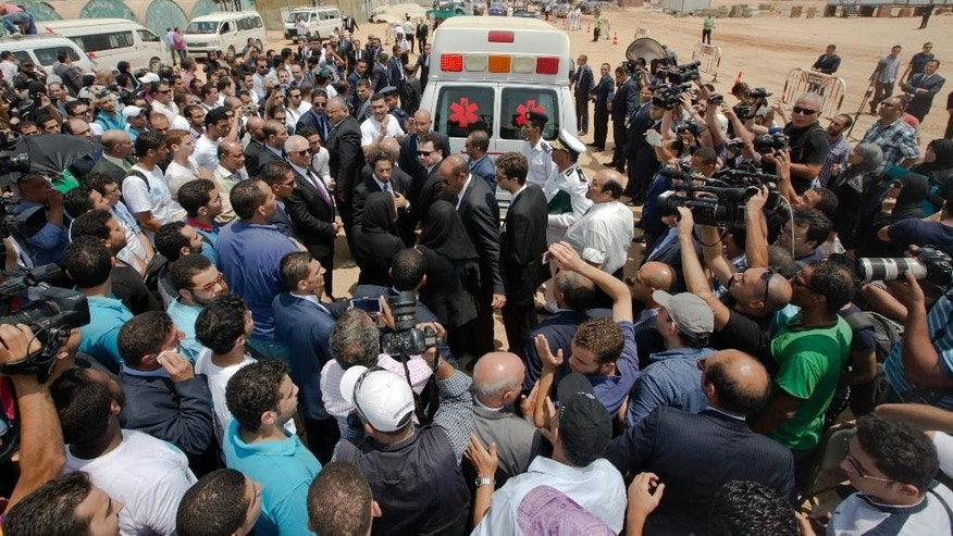 Egyptian mourners surround an ambulance carrying the coffin of Egyptian-American Nobel Laureate Ahmed Zewail during a public funeral ceremony at the site of a science academy founded by Zewail, in 6th of October city, near Cairo, Egypt, Sunday, Aug. 7, 2016. Egypt bid farewell to Ahmed Zewail, the Egyptian-born scientist who won a Nobel Prize in 1999, according him a military funeral with full honors led by President Abdel-Fattah el-Sissi. Zewail, was a science adviser to President Obama who won the 1999 Nobel Prize for his work on the study of chemical reactions over immensely short time scales. (AP Photo/Amr Nabil)