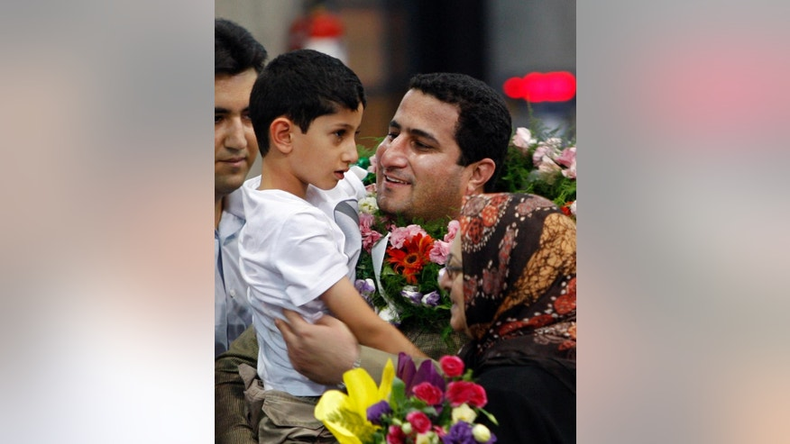 FILE -- In this July 15, 2010 file photo, Shahram Amiri, an Iranian nuclear scientist greets his son Amir Hossein as he arrives to the Imam Khomeini airport after returning from the United States, outside Tehran, Iran. Amiri, who was caught up in a real-life U.S. spy mystery and later returned to his homeland and disappeared, has reportedly been executed under similarly mysterious circumstances. Amiri was reportedly hanged this week and family members held a memorial service for him in the Iranian city of in Kermanshah, 500 kilometers (310 miles) southwest of Tehran. State media in Iran, which has been silent about Amiri's case for years, has not reported his death.  (AP Photo/Vahid Salemi, File)