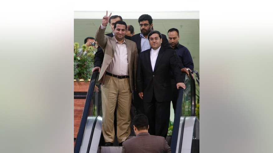FILE -- In this  July 15, 2010 file photo, Shahram Amiri, an Iranian nuclear scientist flashes a victory sign as he arrives to the Imam Khomeini airport just outside Tehran, Iran, from the United States. Amiri, who was caught up in a real-life U.S. spy mystery and later returned to his homeland and disappeared, has reportedly been executed under similarly mysterious circumstances. Amiri was reportedly hanged this week and family members held a memorial service for him in the Iranian city of in Kermanshah, 500 kilometers (310 miles) southwest of Tehran. Then deputy Iranian Foreign Minister Hassan Qashqavi, is at right. (AP Photo/Vahid Salemi, File)