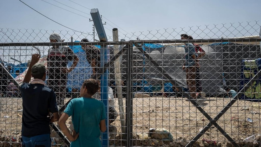Men speak through a fence surrounding an area where newcomers are interrogted at Dibaga camp for internally displaced civilians in Iraq, on August 7, 2016. (AP Photo/Alice Martins)