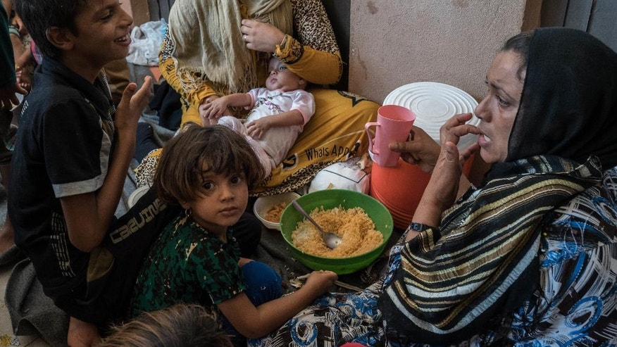Women and children eat on the floor in an overcrowded space at Dibaga camp for internally displaced civilians in Iraq, on August 7, 2016. (AP Photo/Alice Martins)