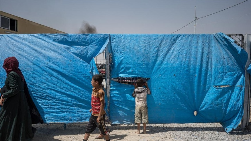A child peeks through a fence surrounding an area where newcomers are interrogted at Dibaga camp for internally displaced civilians in Iraq, on August 7, 2016. (AP Photo/Alice Martins)