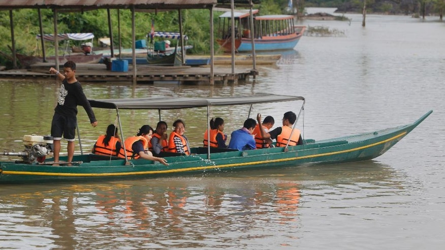 In this June 21, 2016, photo, tourists sit on a wooden boat as they start to cross the Mekong River to close a habitat of dolphin, which is located near the site of Don Sahong dam, near Cambodia-Laos borders, in Preah Romkel village, Stung Treng province, northeast of Phnom Penh, Cambodia. Landlocked Laos is the poorest state in Southeast Asia but by virtue of geography and growing Chinese influence, its secretive authoritarian leaders wield a huge and unaccountable power over a river that winds through six countries. (AP Photo/Heng Sinith)