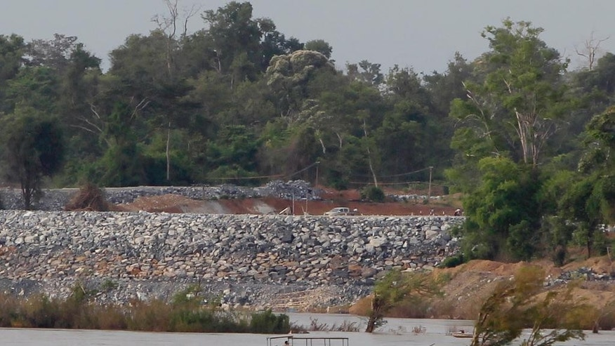 In this June 20, 2016, photo, a fishing boat passes near a construction site of the Don Sahong dam, near Cambodia-Laos borders, in Preah Romkel village, Stung Treng province, northeast of Phnom Penh, Cambodia. Landlocked Laos is the poorest state in Southeast Asia but by virtue of geography and growing Chinese influence, its secretive authoritarian leaders wield a huge and unaccountable power over a river that winds through six countries. (AP Photo/Heng Sinith)