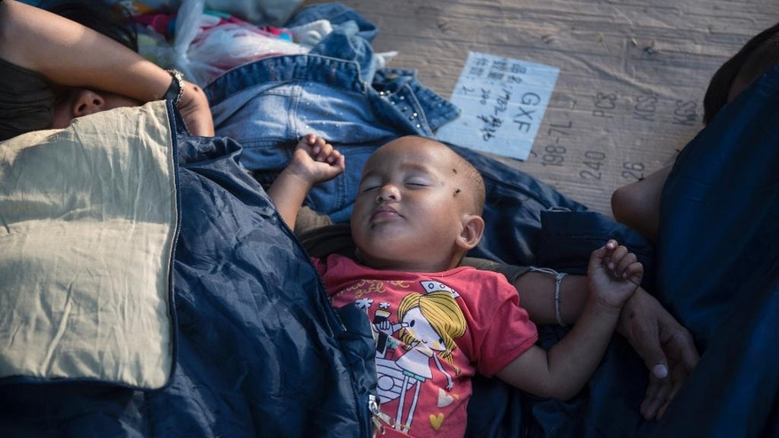 "An Afghan boy sleeps in a park, at the northern Greek city of Thessaloniki, on Saturday, July 9, 2016.  With Turkey in crisis and Europe's borders closed, smugglers in northern Greece are looking forward to a profitable summer. Police say traffickers are using increasingly sophisticated methods _ with motorcycle spotters, ""blind spot"" maps in border surveillance, and even police informants to move refugees stuck here for months in limbo. (AP Photo/Giannis Papanikos)"