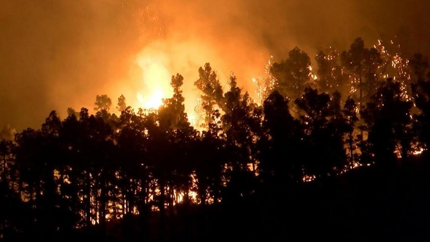 In this image made from video on Saturday, Aug. 6, 2016, a forest fire rages in La Palma on the Canary Islands, Spain. Spanish authorities have evacuated 500 more residents in the path of a five-day-old forest fire on the Atlantic island of La Palma. The regional government for the Canary Islands archipelago says the evacuation of two neighborhoods in the town of Villa de Mazo took place Sunday morning shortly after midnight as the fire spread through the hilly terrain. (Wikono via AP)