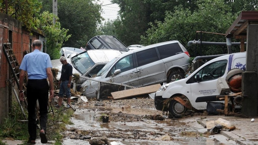 People walk through a street where cars have piled due to overnight flooding in the village of Stajkovci.