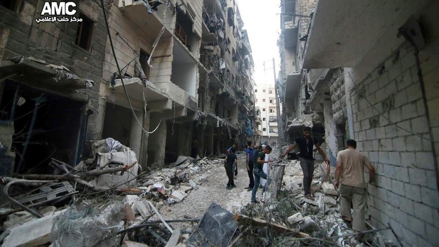 FILE - In this Friday, July. 29, 2016 file photo, provided by the Syrian anti-government activist group Aleppo Media Center (AMC), shows Syrian citizens inspect damaged buildings after airstrikes hit Aleppo, Syria. Fierce fighting and airstrikes continue in Syria's northern city of Aleppo as insurgents try to break a siege on opposition-held eastern districts in a counteroffensive to government advances. But Syria's war, now in its sixth year, is raging beyond Aleppo, claiming dozens of lives every day. (Aleppo Media Center via AP, File)