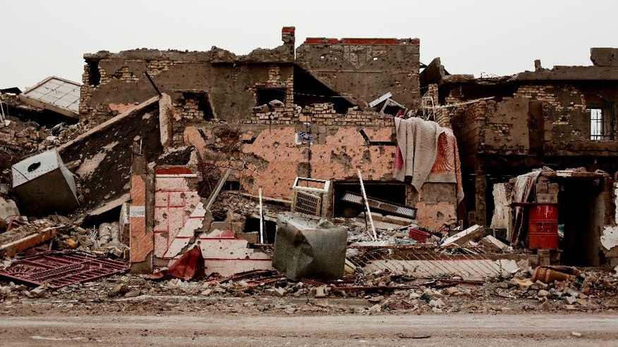 FILE - A family house lies in ruins in the Iraqi city of Ramadi on March 20, 2016, weeks after the city was retaken from the Islamic State group. Entire city blocks were leveled by fighting, airstrikes and by the militants themselves, deliberately blowing up buildings as they fled. Two years ago, just weeks after the fall of Mosul, an Islamic State group push deeper into Iraq's Kurdistan region triggered Iraq's Peshmerga forces to retreat and the U.S.-led coalition to drop the first airstrikes in the fight against the militant group. Since then coalition planes have dropped more than 9,400 bombs on Iraq. The munitions, often called in to closely support advancing forces on the ground, have dramatically changed the fight against IS, allowing Iraqi forces to slowly claw back cities, towns, supply lines and infrastructure. But the fight _ that continues to be largely waged from the air _ has also leveled entire neighborhoods, displaced millions and redrawn the Iraqi map. (AP Photo/Maya Alleruzzo, File)