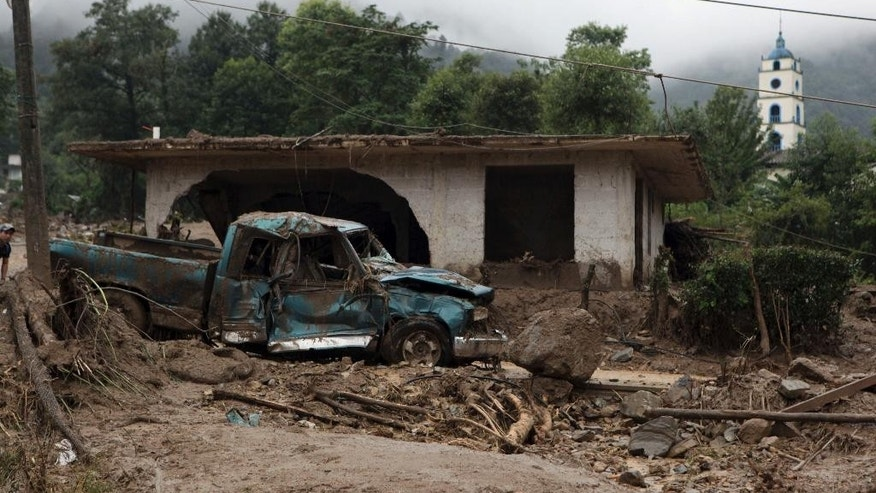 A pickup truck lays destroyed next to a house damaged by a mudslide in Xaltepec, on the mountainous north of Puebla state, Mexico, Sunday, Aug. 7, 2016. The death toll from the remnants of Hurricane Earl grows to more than 30 in Mexico as a new tropical storm forms off the country's Pacific Coast. (AP Photo/Pablo Spencer)