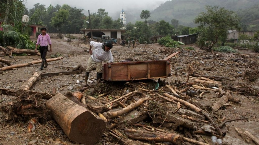 A man inspects furniture that was dragged by a mudslide in Xaltepec, on the mountainous north of Puebla state, Mexico, Sunday, Aug. 7, 2016. The death toll from the remnants of Hurricane Earl grows to more than 30 in Mexico as a new tropical storm forms off the country's Pacific Coast. (AP Photo/Pablo Spencer)