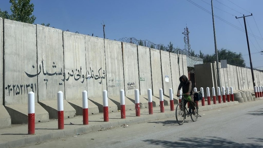 An Afghan man pedals his bicycle past American University of Afghanistan in Kabul, Afghanistan, Monday, Aug. 8, 2016. Five gunmen wearing Afghan military uniforms abducted an American and an Australian in Kabul, a security official said Monday. Sediq Sediqqi, spokesman for the Afghan Interior Ministry, said that the two foreigners were taken from their SUV while driving on Sunday night on a main road near the university. They are believed to be employees of the university, he said. (AP Photo/Rahmat Gul)