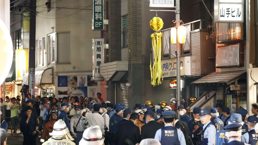 Policemen and fire workers at the site where a man apparently threw Molotov cocktails onto a crowd in Tokyo.