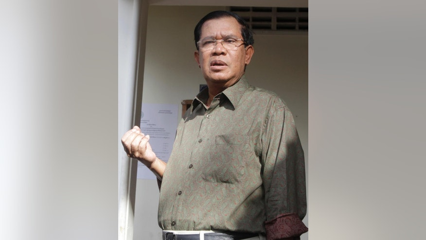 In this June 24, 2016 photo, Cambodian Prime Minister Hun Sen briefs the media after paying a traffic violation at a local police station in Phnom Penh, Cambodia. Hun Sen, who is known for his casual comments, went off track while responding to a Facebook comment on his health to talk about his weight. He said Monday, Aug. 8, 2016, someone had reposted on Facebook a two-year-old video clip, purporting to show he had suffered a stroke. (AP Photo/Heng Sinith)