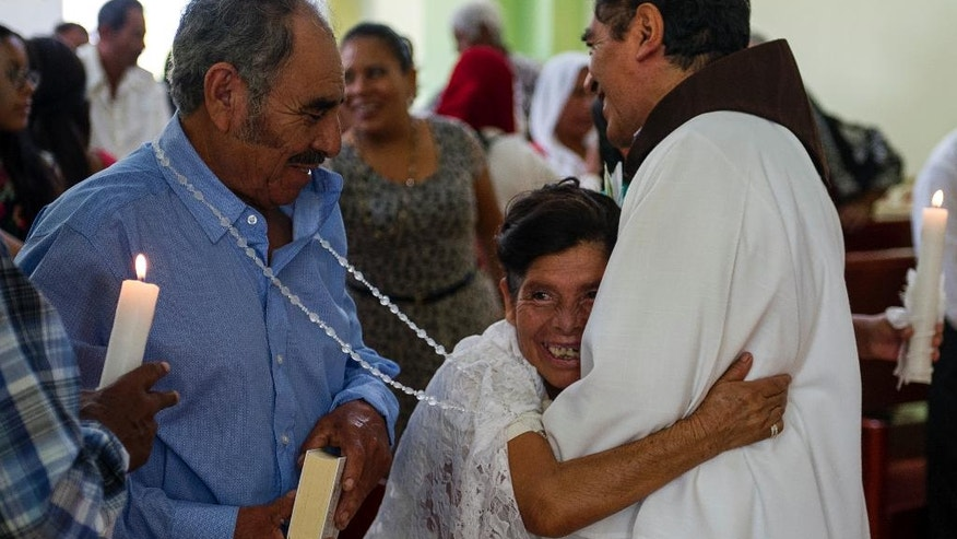 In this July 23, 2016 photo, Francisca Santiago, 65, embraces the Rev. Domingo Garcia Martinez after he wed her and lifelong partner Pablo Ibarra, 75, in Santa Ana, in the Mexican state of Oaxaca. Santiago pulled in the priest for a big hug while a nose-wrinkling smile lit up her face. 'It was beautiful, everything I hoped for,' Santiago said. 'Now we are together with the blessing of God.' (AP Photo/Nick Wagner)