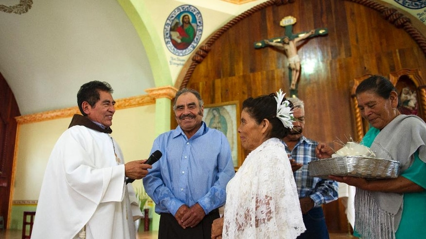 In this July 23, 2016 photo, Francisca Santiago, 65, and her lifelong partner Pablo Ibarra, 75, crack a smile as they exchange wedding vows at the church in Santa Ana, in the Mexican state of Oaxaca. The Rev. Domingo Garcia Martinez performed Ibarra and Santiago's wedding in front of about 250 family and friends. (AP Photo/Nick Wagner)