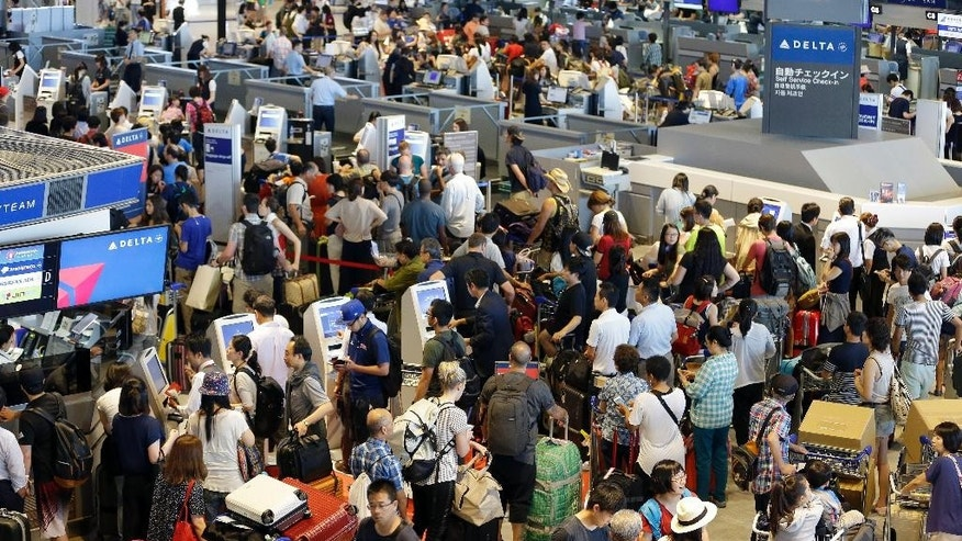 Passengers line up at check-in counter for Delta Air Lines at Narita international airport in Narita, east of Tokyo, Tuesday, Aug. 9, 2016. More than 1,000 people were forced to spend the night at Tokyo's Narita airport because of the computer shutdown that halted Delta Air Lines flights worldwide. (AP Photo/Shizuo Kambayashi)