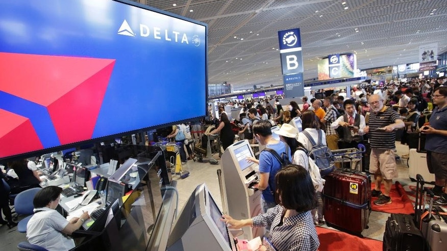 Passengers check in at the Delta Air Lines counter at Narita international airport in Narita, east of Tokyo, Tuesday, Aug. 9, 2016. More than 1,000 people spent the night at the Narita airport because of a computer shutdown that halted Delta Air Lines flights worldwide. (AP Photo/Shizuo Kambayashi)