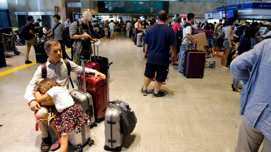 Passengers wait in front of Delta Air Lines counter at Narita international airport in Narita, east of Tokyo, Tuesday, Aug. 9, 2016. More than 1,000 people spent the night at the Narita airport because of a computer shutdown that halted Delta Air Lines flights worldwide. (AP Photo/Shizuo Kambayashi)