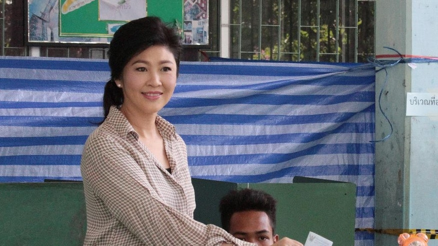 Former Thailand's Prime Minister Yingluck Shinawatra poses as she casts her vote in a national referendum on a new constitution at a polling station in Bangkok, Thailand, Sunday, Aug. 7, 2016. Thais voted Sunday in a referendum on a new constitution that critics say is tailor-made for the military government to stay in control for several years and entrench a new, quasi-democratic system that gives vast powers to appointed officials. (AP Photo/Vicky Ge Huang)