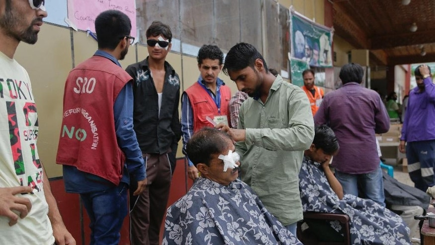 Barbers trim the hair of Kashmiri men wounded by pellets during the recent unrest outside a hospital in Srinagar, Indian controlled Kashmir, Monday, Aug. 8, 2016. Protests and curfew continue across the valley amidst outrage over the killing of a top rebel leader by Indian troops in early July, 2016. (AP Photo/Mukhtar Khan)