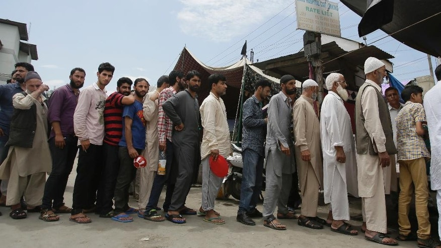 Kashmiri Muslim attendants of patients wait to receive rice distributed outside Kashmir's main hospital in Srinagar, Indian controlled Kashmir, Monday, Aug. 8, 2016. Protests and curfew continue across the valley amidst outrage over the killing of a top rebel leader by Indian troops in early July, 2016. (AP Photo/Mukhtar Khan)