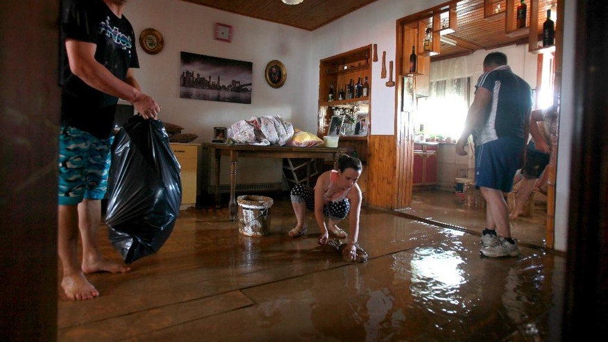 People clean a room in a flooded house after an overnight storm, in the village of Singelic, just east of Skopje, Macedonia, Sunday, Aug. 7, 2016. The Macedonian capital of Skopje has been hit Saturday night by torrential rain and floods that left at least 17 people dead, six missing and sent 60 others to the hospital. (AP Photo/Boris Grdanoski)