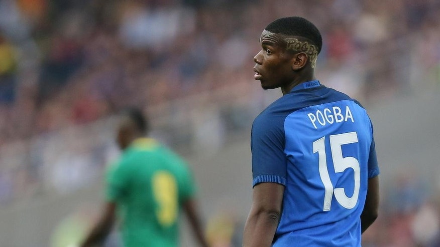 "FILE - In this Monday, May 30, 2016 file photo, France's Paul Pogba looks on during a friendly soccer match between France and Cameroon at the La Beaujoire Stadium in Nantes, western France. Manchester United says Paul Pogba has been granted permission to have a medical examination to finalize his transfer to the English club from Juventus. United made the announcement in a one-line statement on Sunday, Aug. 7, 2016 under the hashtag ""Pogback."" (AP Photo/David Vincent, file)"
