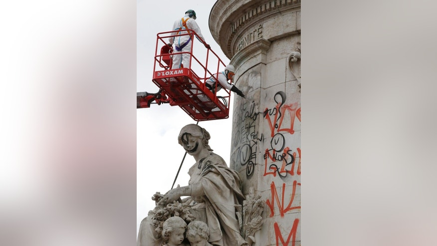Municipality workers remove graffitis from the Republique Statue, Monday, Aug. 8, 2016. Paris city council is cleaning the graffiti and posters off the Place de la Republique statue on the square that became the focal point of mourning after attacks in the French capital. The cleaning of the makeshift memorial, which started earlier this month, is set to be completed by Aug. 11. (AP Photo/Michel Euler)