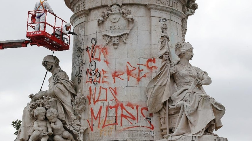 Municipality workers remove graffitis from the Republique Statue in Paris, Monday, Aug. 8, 2016. Paris city council is cleaning the graffiti and posters off the Place de la Republique statue on the square that became the focal point of mourning after attacks in the French capital. The cleaning of the makeshift memorial, which started earlier this month, is set to be completed by Aug. 11. (AP Photo/Michel Euler)