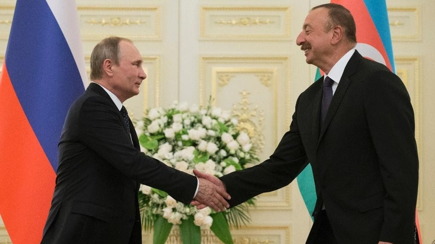 Russian President Vladimir Putin, and Azerbaijan's President Ilham Aliyev greet each other during their meeting in Baku, Azerbaijan, Monday, Aug. 8, 2016. Leaders of Azerbaijan, Iran, Russia are meeting to focus on boosting trade. (AP Photo/Alexander Zemlianichenko, pool)