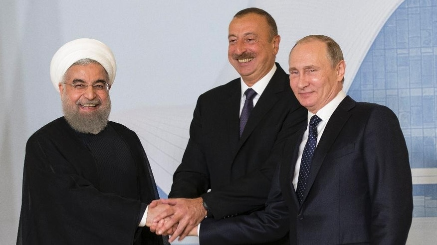 Iranian President Hassan Rouhani, left, Azerbaijan's President Ilham Aliyev, center, and Russian President Vladimir Putin pose for a photo during their meeting in Baku, Azerbaijan, Monday, Aug. 8, 2016. Leaders of Azerbaijan, Iran, Russia are meeting to focus on boosting trade. (AP Photo/Alexander Zemlianichenko, pool)