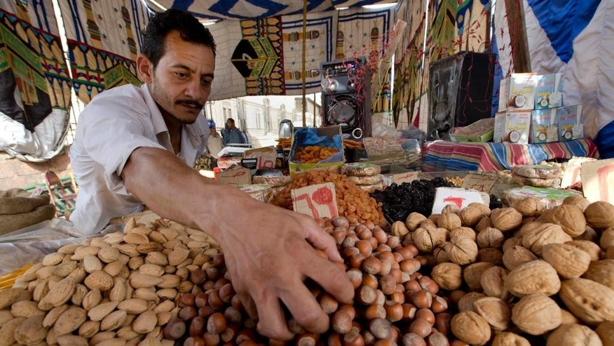 FILE -- In this June 14, 2016 file photo, an Egyptian vendor arranges his goods at a market in the neighborhood of Sayeda Zeinab, in Cairo, Egypt. Three Egyptian dailies said Monday, Aug 8, 2016, that Cairo was proposing to IMF delegates an 18-month reform program in return for a $12 billion loan over three years to shore up its economy, but that differences remained between the two sides on how to proceed. Egypt is struggling to keep its economy afloat, amid a slump in tourism, foreign currency shortages and double digit inflation and unemployment. President Abdel-Fattah el-Sissi has repeatedly vowed in recent days to shield the poor and middle class from a virtually inevitable wave of price hikes when reforms are implemented. (AP Photo/Amr Nabil, File)