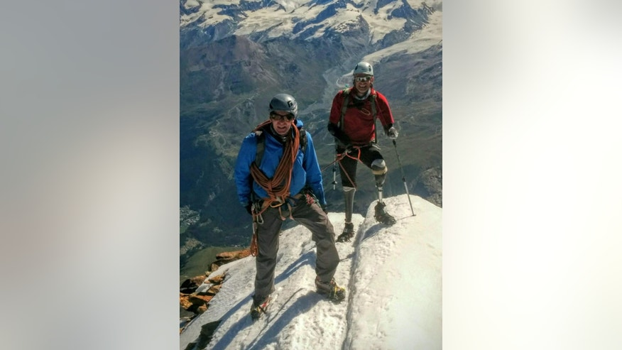 In this handout picture taken Thursday Aug. 4, 2016 British quadruple amputee mountaineer Jamie Andrew,  right,  and  Steve James, who accompanied him,  stand on Matterhorn Mountain in Switzerland.  The  British mountaineer who climbed Switzerland's iconic Matterhorn says he is the first quadruple amputee to do so. Jamie Andrew lost his hands and feet to frostbite after becoming trapped in a snowstorm while mountaineering in France 17 years ago. (Courtesy of Jamie Andrew via AP)