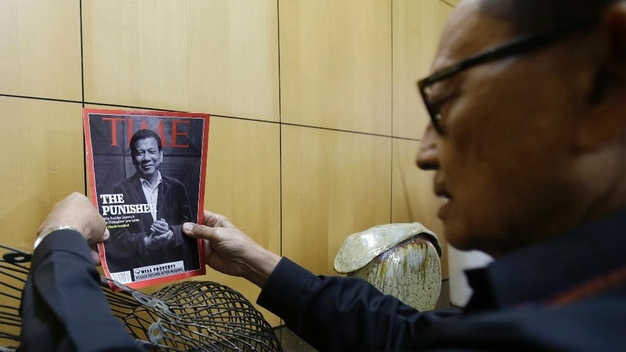 Former Philippine President Fidel Ramos holds a magazine bearing an image of current President Rodrigo Duterte before holding a press conference while waiting for his flight at Manila's International Airport in suburban Pasay, south of Manila, Philippines, Monday, Aug. 8, 2016. Ramos flew to Hong Kong on Monday for talks with long-standing contacts after being asked by current President Rodrigo Duterte to travel to China and start discussions on the South China Sea. (AP Photo/Aaron Favila)