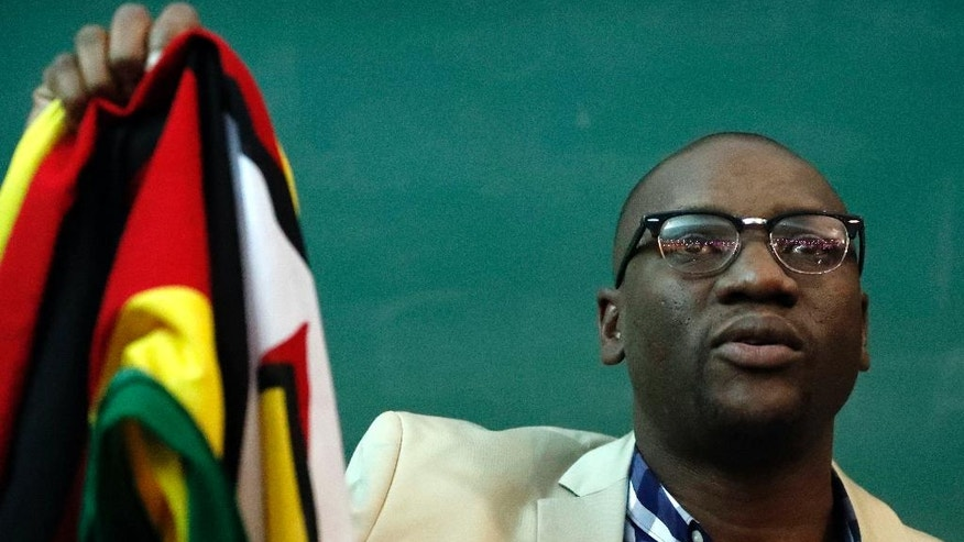 FILE - In this July 28, 2016 file photo, Zimbabwean pastor Evan Mawarire, holds his country's flag before addressing supporters at the University of the Witwatersrand in Johannesburg, South Africa. Mawarire, who is using social media to take on President Robert Mugabe's government, says he is afraid for his life and wants his countrymen to do everything possible to avoid bloodshed in their quest to reform the southern African country.  In an interview with the Associated Press in Johannesburg on Monday, Aug. 8, 2016, he said Mugabe's ZANU-PF party was eating itself alive and there is very little that citizens of the country can do to fight it. (AP Photo/Themba Hadebe, file)