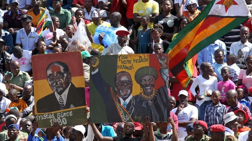 Supporters of Zimbabwean President Robert Mugabe carry a portrait of him and his wife Grace during a gathering to honor the country's dead heroes, at the National Heroes Acre in Harare, Monday, Aug. 8, 2016. The commemorations are held annually to honor the southern African country's dead heroes, particularly those who fought in the 1970s independence war. Leaders of the Zimbabwe National Liberation War Veterans Association, who broke away from the 92-year-old president in July, boycotted the event. (AP Photo/Tsvangirayi Mukwazhi)