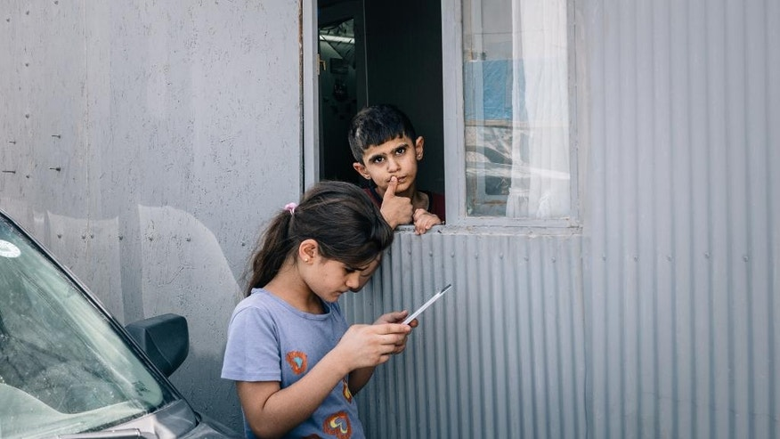 In this Aug. 8, 2016 photo, Raad Bahnam Samaan's son looks out the window as his sister stands outside the caravan where their family has been living in Irbil, Iraq. The family was forced to flee their hometown of Qaraqosh when Islamic State militants took control of the place two years ago. (AP Photo/Alice Martins)