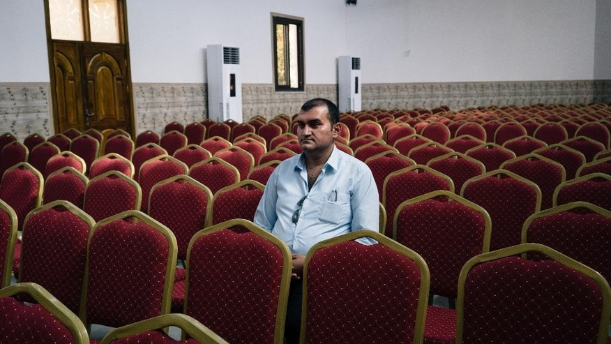 In this Monday, Aug. 8, 2016 photo, Rami Hannah Qaroumi, an Iraqi Christian from Qaraqosh, sits in the Assyrian church where he works in Irbil, Iraq. Rami fled to France with his family, but after a few months decided to come back to Iraq. He is now once again considering going back to Europe. (AP Photo/Alice Martins)