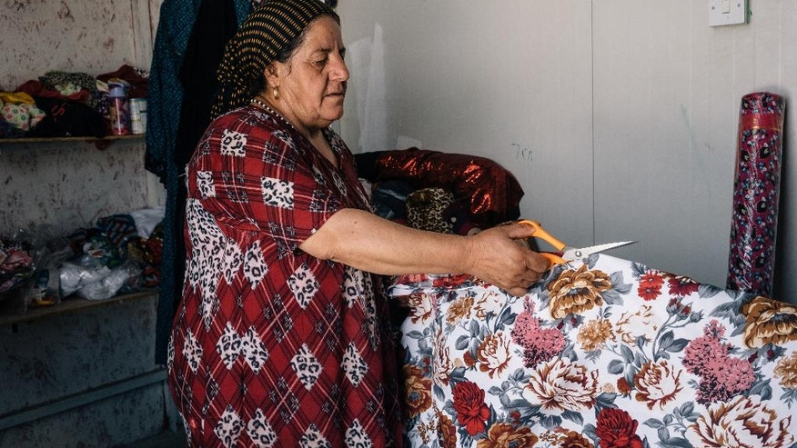 In this Monday, Aug. 8, 2016 photo, Sabryia, a Christian from Qaraqosh, cuts a fabric at her small shop in a camp for Iraqi Christians displaced by war in Irbil, Iraq. She fled her town when Islamic State militants took control two years ago. As operations to retake the militant-held city of Mosul ramp up, Iraqi Christians displaced from the area by the Islamic State group say even a military defeat of the extremists in Iraq will not make the country safe for minorities again. (AP Photo/Alice Martins)