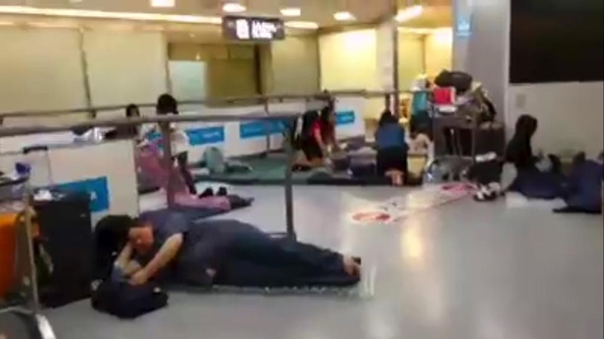 In this image made from video, stranded passengers lay on air mattresses at the Narita international airport in Narita outside Tokyo, early Tuesday, Aug. 9, 2016. Jeff Quigley, an American who lives in Japan and Indonesia, was one of thousands of passengers caught up in the worldwide Delta Air Lines shutdown. As day stretched into night, then overnight and the next morning, the 30-year-old venture capitalist posted live video updates on his Facebook page during what ended up being a nearly 20-hour delay at Narita airport outside Tokyo. (Jeff Quigley via AP)
