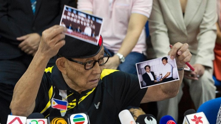 Former Philippine President Fidel Ramos holds up what he says are photos of Chinese President Xi Jinping when he visited the Philippines in his youth during a press briefing at the Philippines consular office in Hong Kong, China, Tuesday, Aug. 9, 2016. Former Philippine President Fidel Ramos flew to Hong Kong on Monday for talks aimed at rekindling ties with China that have been strained by long-seething disputes in the South China Sea.(AP Photo/Ng Han Guan)